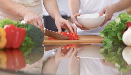 Close-up of four human hands are cooking in a kitchen. Friends having fun while preparing fresh salad. Vegetarian, healthy meal and friendship concept