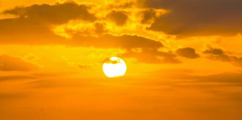 Fotobehang - Sun shining through the clouds at sunset