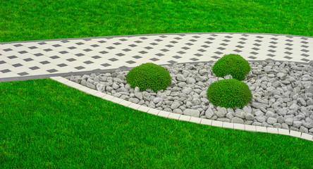 Moderner Steingarten mit Gartenweg aus Betonpflaster im Panoramaformat - Modern rock garden with garden path made of concrete pavement in panoramic format