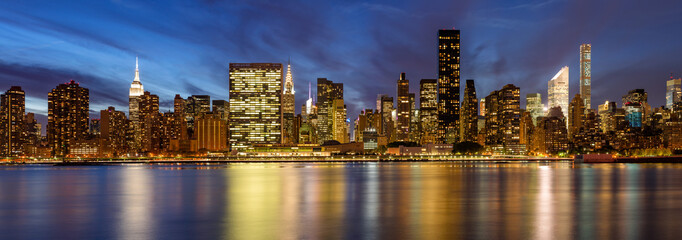 Wall Mural - Panoramic view of Midtown East skyscrapers from the East River at twilight. Manhattan, New York City