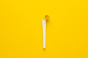 paper and plastic party horn on the yellow background