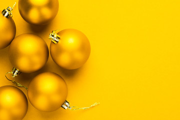 Christmas tree decoration balls on yellow background with copy space