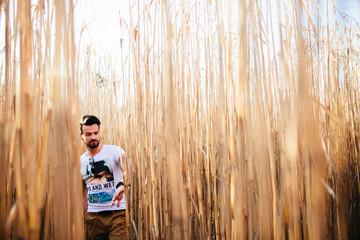 Junger Mann mit T-Shirt in Strohfeld