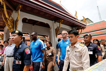 Leicester City soccer club's captain Wes Morgan and goalkeeper Kasper Schmeichel walk as they visit the Emerald Buddha temple in Bangkok