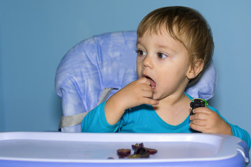 Baby boy eating black grapes