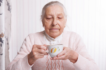An elderly woman drinks tea at home. Senior woman holding cup of tea in their hands at table closeup
