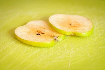 Two thin green apple slices on a cutting board turned brown due to the oxidation process close up stock image.