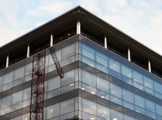 modern glass and black office building with reflection of a construction crane and blue sky