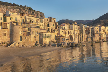 Old houses with reflections in water in late afternoon, Cefalu, Sicily, Italy