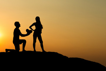 Silhouette of attractive confident half naked man propose marriage to bikini womanSilhouette of attractive confident half naked man propose marriage to bikini woman
