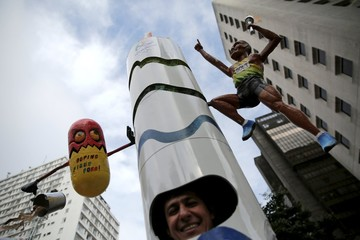 """A runner is dressed in a costume depicting the Rio 2016 Olympic torch before the annual """"Sao Silvestre Run"""" in Sao Paulo"""