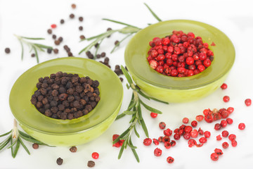 Black and red peppers in green bowls on white background