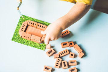 Close up of child's hands playing with real small clay bricks at the table. Toddler having fun and building out of real small clay bricks. Early learning. Developing toys. Construction concept