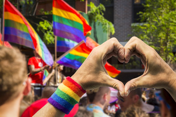 Supporting hands make heart sign and wave in front of a rainbow flags flying on a float of a summer gay pride parade