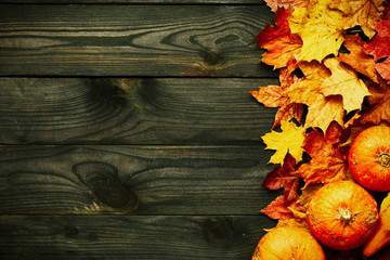 Autumn leaves and pumpkins over old wooden background
