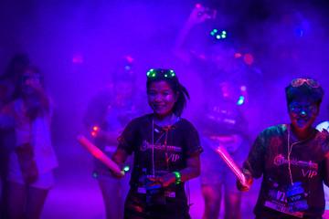 Participants run through coloured powder during the Blacklight Run Thailand in Bangkok