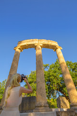 Travel woman photographer takes pictures of ruins Philippeion columns in Ancient Olympia, Historical Site, Peloponnese, Greece. Blonde female photographing a Greek Temple. Europe summer travel concept