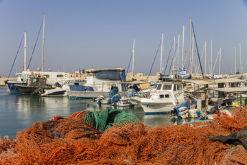 An orange fishnet in front of Ships anchoring at the Jaffa port