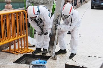Trabajadores retiran tuberías de amianto del interior de un puente en San Sebastian (España)