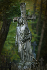 Cross and angel statue on gravestone at cemetery. Rest in peace. In memoriam