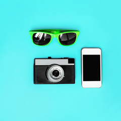 Fashion accessory, sunglasses, vintage camera with a smartphone over a blue background