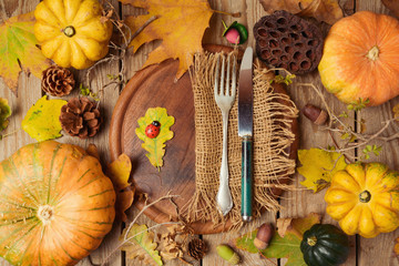 Autumn background with fall leaves and pumpkin over wooden table. View from above