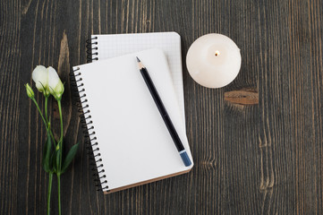 Blank notebooks, lit candle