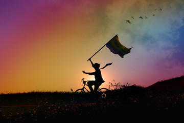 freedom of expression for gay and homosexual concept, Silhouette of happy person on bicycle, hold and raised arms with flag in rainbow sunrise or sunset sky