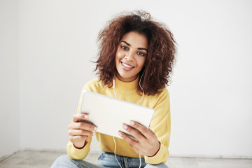 Beautiful african girl in headphones smiling looking at camera holding tablet sitting on floor over white background.