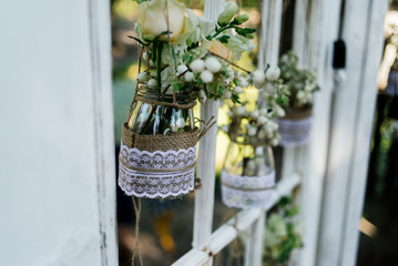 Little wedding floral decorations in rustic style hang in jars decorated with sacking and lace