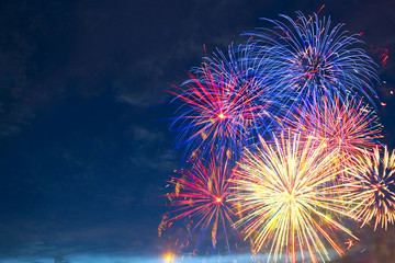 Fireworks of various colors bursting against a black