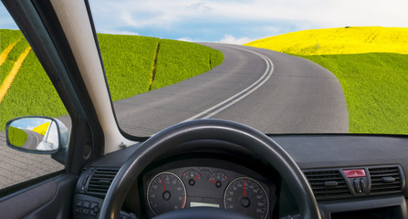 View from the interior of a car driving on an asphalt road