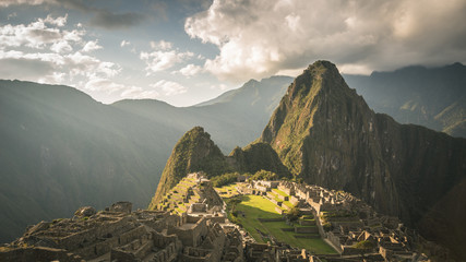 Machu Picchu archeological site, wide angle view from the terraces above with scenic sky. Toned image.