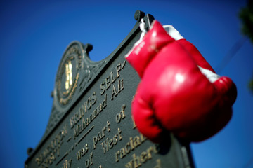 Boxing gloves are seen hanging on a historical marker outside Muhammad Ali's childhood home in Louisville, Kentucky, U.S.
