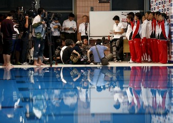 Members of Japan's synchronised swimming team speak to media after training session at pool in Tokyo