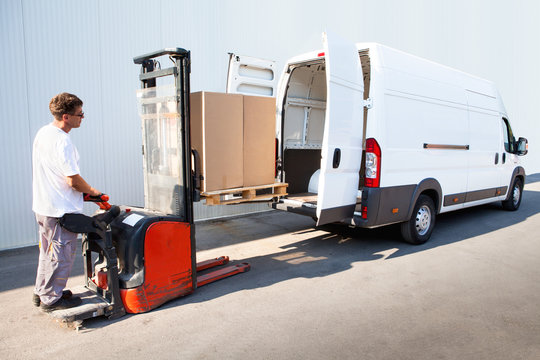 Courier is loading the van with parcels.