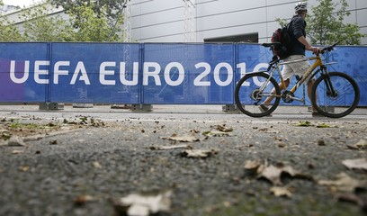 A man walks with his bicycle past a banner reading 'UEFA EURO 2016' at the Euro 2016 International Broadcast Center in Paris
