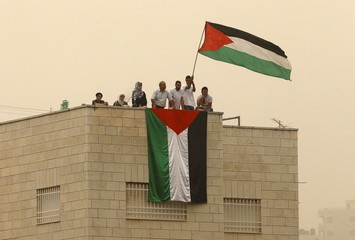 Fans of Palestine, atop the roof of a building, watch the 2018 World Cup qualifying soccer match against the United Arab Emirates, at Faisal al-Husseini Stadium, in the occupied West Bank town of Al-Ram near Jerusalem