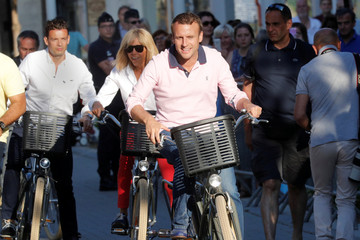 French President Emmanuel Macron and his wife Brigitte Trogneux ride their bicycles as they leave their home in Le Touquet