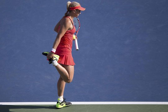 Lisicki of Germany stretches a leg muscle during her fourth round match against Halep of Romania at the U.S. Open Championships tennis tournament in New York