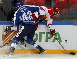 Finland's Melart sends Russia's Andronov into boards during their Channel One Cup ice hockey game in Moscow