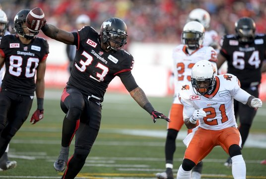 Calgary Stampeders' Jerome Messam crosses the goal line for a touchdown against the BC Lions'  Ryan Phillips during first half of the CFL western semi-final football game in Calgary