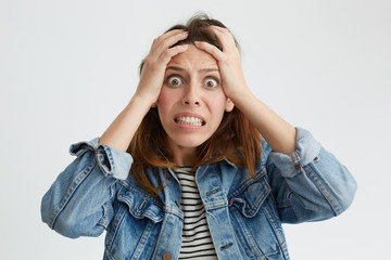Portrait of shocked terrified woman with dark eyes popped out clenching her teeth holding hands on head looking in despair into camera isolated over white background. Woman having frustration