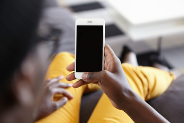 Back view of hipster guy lying at cozy sofa holding modern smartphone with blank screen for your text messaging and looking photos online. Cropped view of dark-skinned male holding mobile phone