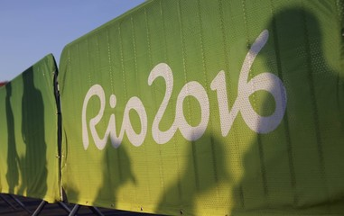 Fans' shadows are projected on a fence in the Olympic Park in Rio de Janeiro