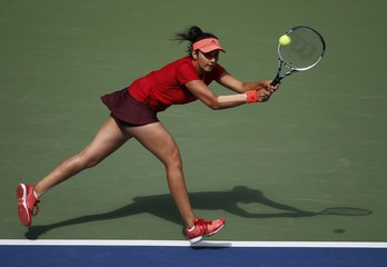 Mirza of India chases down a return with playing partner Hingis of Switzerland as they face Dellacqua of Australia and Shvedova of Kazakhstan in the women's doubles final match at the U.S. Open Championships tennis tournament in New York