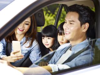 asian family enjoying a car ride, focus on the little girl.