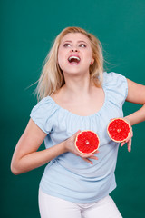 Woman holds grapefruit citrus fruit on breast