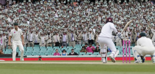 Fans dressed as late cricket player and commentator Richie Benaud wear suits, grey wigs and prop microphones, as they pay tribute to him during the third cricket test between Australia and the West Indies at the SCG in Sydney