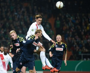 Bremen's Vestergaard heads for the ball with Cologne's Soerensen and Risse during their German Cup (DFB Pokal) second round soccer match in Bremen